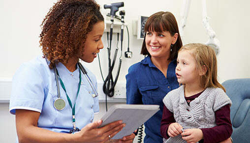 Une docteure, tablette en main, rend visite à une mère et sa petite fille.