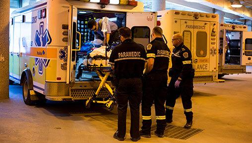 Des travailleurs paramédicaux hissent une civière dans une ambulance.
